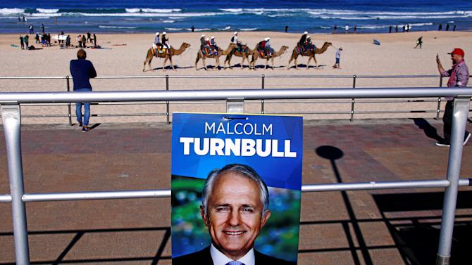 Tourists ride camels along Bondi Beach near a poster promoting the Australian Prime Minister Malcolm Turnbull in front of a voting station, located in the Bondi Surf Lifesavning Club, in Sydney, Australia