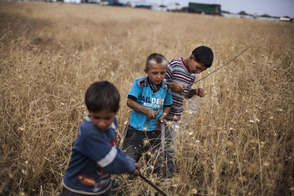 Syrian boys play near a refugee camp on the border with Turkey, near Azaz village, Syria, Sunday, Sept. 30, 2012. (AP Photo/ Manu Brabo)