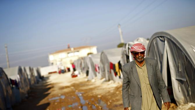 A Kurdish refugee man from the Syrian town of Kobani walks between tents in a camp in the southeastern town of Suruc