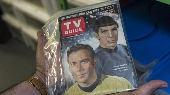 """In this Friday, Nov. 30, 2012 photo, James Comisar holds an original TV Guide issue featuring William Shatner, and Leonard Nimoy of """"Star Trek."""" The item is part of his television memorabilia collection in a temperature- and humidity-controlled warehouse in Los Angeles. (AP Photo/Damian Dovarganes)"""