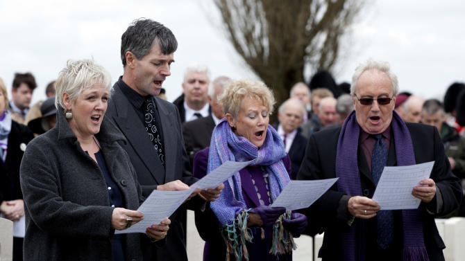 Relatives of British World War One solider Lieutenant John Harold Pritchard sing together during a ceremony at the H.A.C. cemetery in Ecoust-St-Mein, France on Tuesday, April 23, 2013. Almost 100 years after they were killed in action, Lieutenant John Harold Pritchard and Private Christopher Douglas Elphick were re-interred with full military honors in a private ceremony. Almost 100 years after they were killed in action, Lieutenant John Harold Pritchard and Private Christopher Douglas Elphick were re-interred with full military honors in a private ceremony. Lieutenant Pritchard was killed in action on May 15, 1917 during an enemy attack near Bullecourt, France and his remains were found in a field near the site in 2009. His body was eventually identified by a silver bracelet with his name engraved on it. Private Elphick was born in Dulwich, South London in 1889. He was killed in action on May 15, 1917 during an enemy attack near Bullecourt, France and his remains were found in a field near the site in 2009. His body was eventually identified by a signet ring bearing his initials. At left is great niece Janet Shell and second right is great niece Jennifer Sutton. (AP Photo/Virginia Mayo)