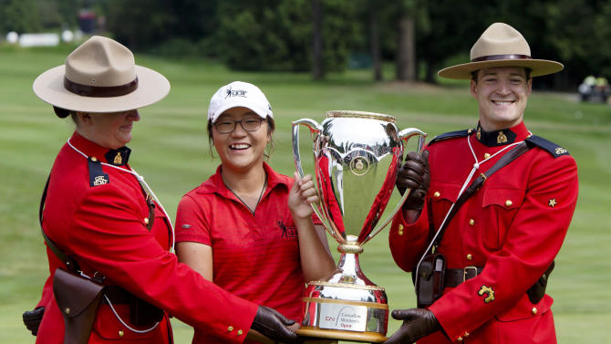 Lydia Ko, of New Zealand poses with the trophy with two members of the Royal Canadian Mounted Police after winning the LPGA Tour's Canadian Women's Open golf tournament, Sunday, Aug. 26, 2012, at the Vancouver Golf Club in Coquitlam, British Columbia. (AP Photo/The Canadian Press, Jonathan Hayward)