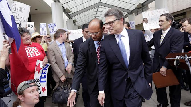 FILE - In an Aug. 19, 2014 file photo, Texas Gov. Rick Perry, front right, is escorted away from the Blackwell Thurman Criminal Justice Center, in Austin, Texas. Just when Perry was feeling like governor non grata, a felony indictment accusing him of abusing his power has energized Texas conservatives, who claim it's a politically motivated attack in an important election year. It's also put the spotlight back on Perry, who is trying to rehabilitate his political image before leaving office in January and convince would-be 2016 Republican primary voters across America he's worth a second look following an embarrassing White House bid three years ago. (AP Photo/Eric Gay, File)