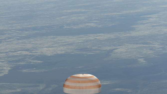 In this image provided by NASA the Soyuz spacecraft is seen as it lands with Expedition 35 Commander Chris Hadfield of the Canadian Space Agency, NASA Flight Engineer Tom Marshburn and Russian Flight Engineer Roman Romanenko of the Russian Federal Space Agency in a remote area near the town of Zhezkazgan, Kazakhstan, on Tuesday, May 14, 2013.  Hadfield, Marshburn and Romanenko returned from five months onboard the International Space Station where they served as members of the Expedition 34 and 35 crews. (AP Photo/NASA, Carla Cioffi)