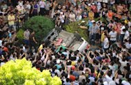 Protesters overturn a car near the local government office compound in Qidong on July 28. Protesters in a restive east China city remained off the streets amid heavy police deployment, a day after violent clashes over fears of pollution from a paper factory