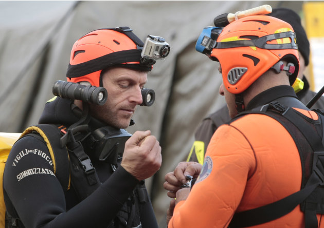Italian divers chat as they prepare to head out to the cruise ship Costa Concordia, as it lays on its side after running aground off the tiny Tuscan island of Giglio, Italy, Thursday, Jan. 19, 2012.
