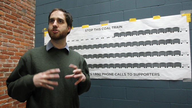 In this photo taken Oct. 23, 2012, Matt Petryni, a community organizer with RE Sources for Sustainable Communities, talks in front of a chart showing how many personal phone calls the group has made in an attempt to stop a coal export terminal from being built nearby, in Bellingham, Wash. The progressive college town of Bellingham is at the center of one of the fiercest environmental debates in the region: should the Northwest become a hub for exporting U.S. coal to Asia? A proposal to build one of as many as five coal terminals here has divided the town, pitting union and businesses that welcome jobs against environmentalists who worry about coal dust and greenhouse gas emissions. A trade group is running TV ads touting the projects, while numerous cities such as Seattle and Portland are opposing coal trains through their communities. (AP Photo/Elaine Thompson)