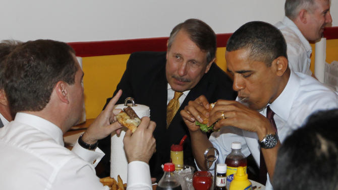 "FILE - In this June 24, 2010, file photo, President Barack Obama and Russia's President Dmitry Medvedev eat hamburgers as they make an unscheduled visit to Ray's Hell Burger in Arlington, Va. Turning 50 is hard enough. But it's got to be even harder when you're president, because the whole world knows about it. The president has a habit of sampling local greasy-spoon delicacies _ whether it's burgers, chili dogs, pastries or all of them _ on trips outside of Washington. He once said he and the first lady would have to figure out how to resist ordering the White House pastry chef's pie every night ""because whatever pie you like, he will make it and it will be the best pie you have ever eaten."" (AP Photo/Charles Dharapak, File)"