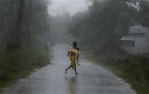 A girl runs for shelter in heavy rain brought by Cyclone Phailin in Ichapuram