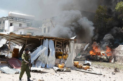 A Somali policeman walks past a burning car on April 14, 2013, in Mogadishu