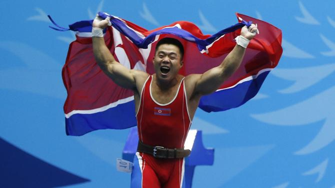 North Korea's Kim Un Guk celebrates after breaking his second world record of the night and winning a gold medal for the men's 62kg weightlifting competition at the Moonlight Garden Venue during the 17th Asian Games in Incheon