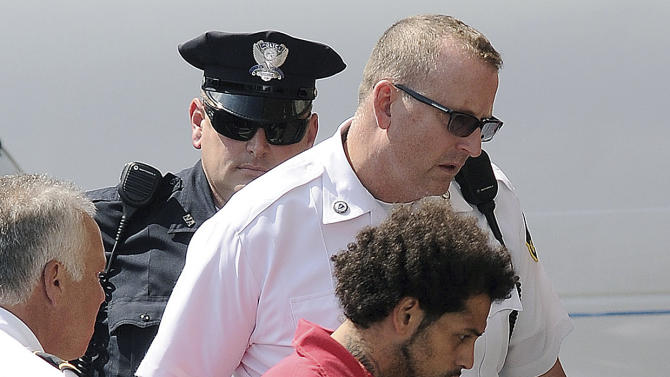Carlos Ortiz is led into Attleboro District Court for his arraignment on weapons charges, Friday, June 28, 2013 in Attleboro, Mass. Ortiz was arrested Wednesday in Bristol, Conn., in connection with the murder case against former New England Patriots tight end Aaron Hernandez , now charged in the murder of Odin Lloyd. (AP Photo/The Sun Chronicle, Mark Stockwell) MAGS OUT. MANDATORY CREDIT.