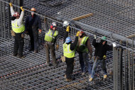 In this photo of Dec. 29, 2011, construction workers lift a steel bar for the foundation of the World Trade Center Transportation Hub in New York. The average number of people seeking unemployment benefits in the past month fell to the lowest level in three and a half years, a positive sign for hiring one day ahead of Friday's December employment report. (AP Photo/Mark Lennihan)
