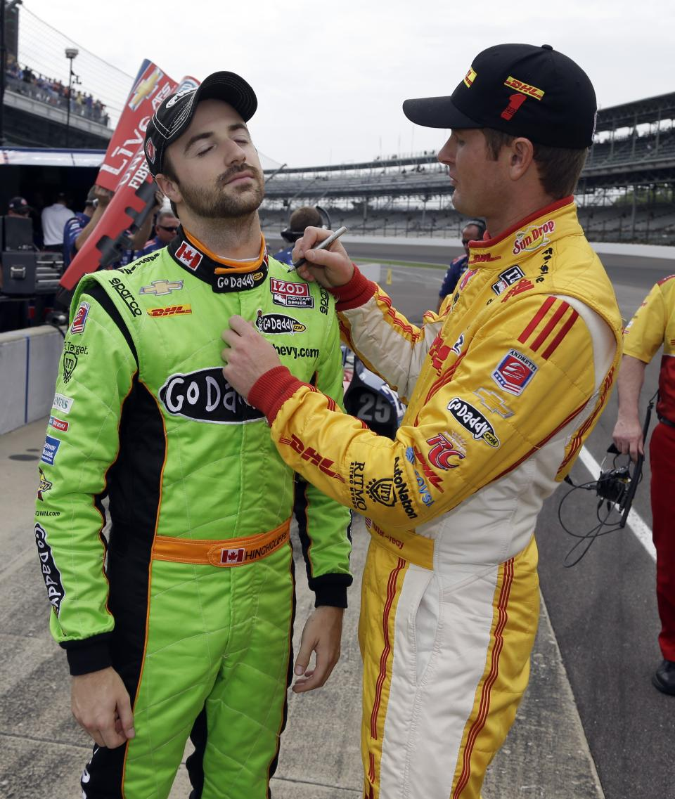 Ryan Hunter-Reay, right, jokingly autographs the driving suit of teammate James Hinchcliffe, of Canada, during practice for the Indianapolis 500 auto race at the Indianapolis Motor Speedway in Indianapolis, Friday, May 17, 2013. (AP Photo/Darron Cummings))