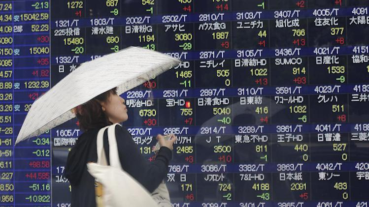 A woman looks at an electronic stock indicator of a securities firm in the rain in Tokyo, Friday, June 6, 2014. Asian stocks were mostly indifferent on Friday to the unveiling of a big stimulus package from the European Central Bank as investors awaited the U.S. jobs report for May. (AP Photo/Eugene Hoshiko)