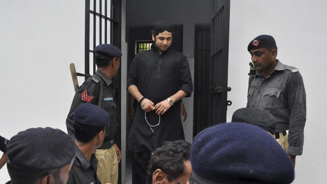 FILE - In this Friday, June 7, 2013, file photo, Shahrukh Jatoi, top center, convicted of killing 20-year-old Shahzeb Khan, is escorted by members of the police to an Anti-Terrorism court in Karachi, Pakistan. The family of a Pakistani student whose death sparked outrage against the abuse of power by the wealthy has decided to pardon the men convicted in his killing, their lawyer said Monday, Sept. 9, 2013. The family filed an affidavit with the court several days ago pardoning the men accused of killing their son, Shahzeb Khan, the lawyer Mehmood Alam Rizvi said. (AP Photo/Shakil Adil, File)