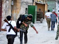 Syrian rebels carry a comrade who was wounded during clashes with government troops in the Salhin district of the northern city of Aleppo