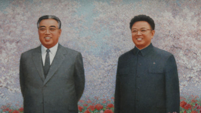 """A family poses for a picture in front of portraits of the late leaders Kim Il Sung and Kim Jong Il at a festival for the """"Kimilsungia"""" flower to mark 100 years since the birth of North Korea's late leader in Pyongyang, North Korea, Tuesday, April 17, 2012. (AP Photo/Vincent Yu)"""