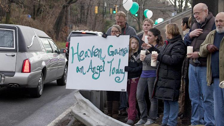 Friends and co-workers hold a sign as the hearse and funeral procession for James Mattioli, 6, who died in the Sandy Hook Elementary School shootings, approaches the St. John's Cemetery Tuesday, Dec. 18, 2012, in Darien, Conn. Adam Lanza walked into Sandy Hook Elementary School in Newtown Dec. 14,  and opened fire, killing 26 people, including 20 children. Tuesday, Dec. 18, 2012. (AP Photo/Craig Ruttle)
