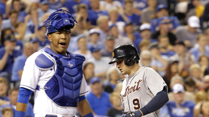 Detroit Tigers' Nick Castellanos (9) runs past Kansas City Royals catcher Salvador Perez to score on a throwing error by second baseman Omar Infante during the fifth inning of a baseball game Friday, Sept. 19, 2014, in Kansas City, Mo. (AP Photo/Charlie Riedel)