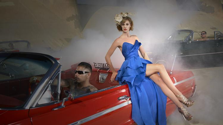 "Kyle models a British couture hat while posing with a vintage American car on ""America's Next Top Model."""