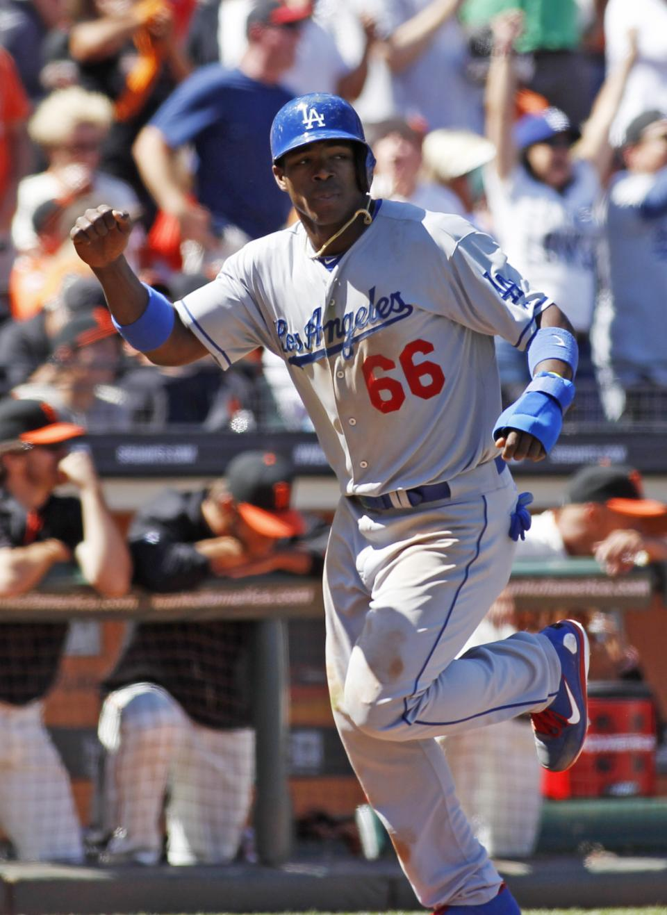Los Angeles Dodgers' Yasiel Puig scores on an A.J. Ellis double against the San Francisco Giants during the ninth inning of a baseball game in San Francisco, Sunday, July 7, 2013. (AP Photo/George Nikitin)
