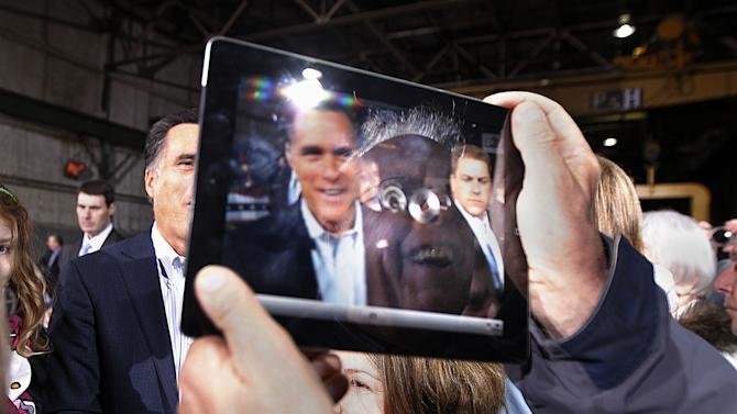 A supporter's reflection and the image of Republican presidential candidate, former Massachusetts Gov. Mitt Romney, are seen on the screen of his iPad as he photographs Romney, greeting supporters at American Posts in Toledo, Ohio, Wednesday, Feb. 29, 2012. (AP Photo/Gerald Herbert)