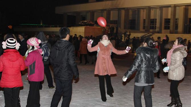 "North Koreans play with a balloon as they wait outside Pyongyang stadium for the countdown to the new year on Monday, Dec. 31, 2012 , Pyongyang, North Korea. North Koreans celebrated the arrival of the new year, marked as ""Juche 102"" on North Korean calendars. ""Juche"" means ""self reliance,"" the North Korean ideology of independence promoted by North Korean founder Kim Il Sung, and modern-day North Korean calendars start with the year of his birth in 1912. (AP Photo/Kim Kwang Hyon)"
