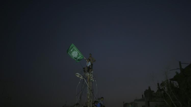 Palestinians stand atop an electrical pole after power was cut in the area during an Israeli offensive, in the Shejaia neighborhood east of Gaza City
