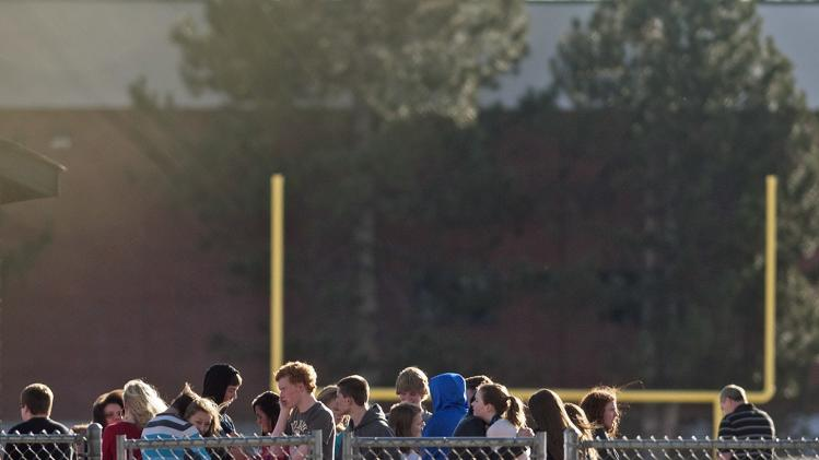 Students gather outside Arapahoe High School, after a student opened fire in the school in Centennial, Colorado