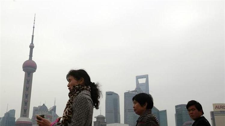 People walk past in the Pudong business district in Shanghai, in this picture taken March 15, 2011. REUTERS/Nicky Loh/Files