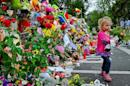 Leila de Wet, two and a half years old, carries flowers as she walks past a wall of flowers laid by mourners outside Nelson Mandela's home in Houghton, Johannesburg, on December 7, 2013