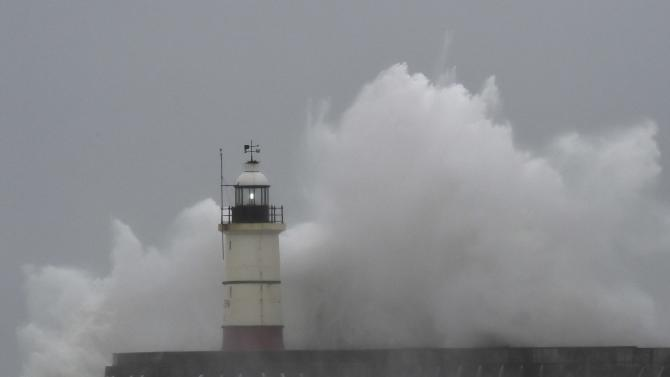 Waves crash against the harbour wall and light beacon at Newhaven in southern England
