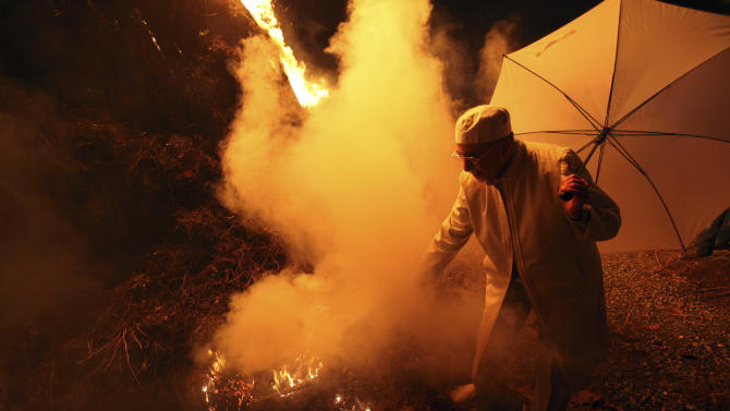 An Iranian Zoroastrian priest sets fire to an already prepared pile of wood, in the Sadeh festival, an ancient Zoroastrians' feast celebrating the creation of fire, outside the capital of Tehran, Iran, Tuesday, Jan. 29, 2013. Followers of Iran's minority Zoroastrian religion gathered after sunset to mark Sadeh, an ancient mid-winter feast dating to Iran's pre-Islamic past that is also drawing new interest from Muslims. (AP Photo/Vahid Salemi)