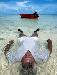 An man relaxes in the waters off Tuvalu as rising sea levels inundate many of his country&#39;s low islands. Tiny Pacific nations which are most at threat from rising seas have vowed to dump diesel and other dirty expensive fuels blamed for causing global warming and replace them with clean sources