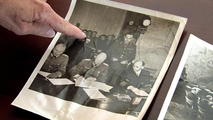 """In this Wednesday, May 2, 2012 image taken from video, Julia Kennedy Cochran, daughter of former AP Paris bureau chief Ed Kennedy, points to her father in a picture taken during the German surrender in 1945, at her home in Bend, Ore. Kennedy was dismissed by The AP after he became the first journalist to file a firsthand account of German officials surrendering unconditionally to Allied commanders at a former schoolhouse in Reims, France. Sixty-seven years later, AP President and Chief Executive Officer Tom Curley said that Kennedy was right to stand up to the censors, and should have been commended, not fired. Cochran said she was """"overjoyed,"""" that the AP had taken an interest in exonerating him. """"I think it would have meant a lot to him,"""" she said. (AP Photo/Rick Bowmer)"""