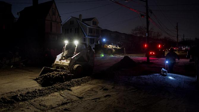 A front loader works to remove sand and debris as night falls on the Rockaway neighborhood in the Queens borough, of New York, Sunday, Nov. 11, 2012, in the wake of Superstorm Sandy. (AP Photo/Craig Ruttle)
