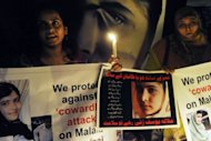 Pakistani civil society activists carry candles to pay tribute to gunshot victim Malala Yousafzai and protest against her assassination attempt, in Lahore. Pakistani doctors on Wednesday removed a bullet from the 14-year-old child campaigner shot by the Taliban in a horrific attack condemned by national leaders and rights activists