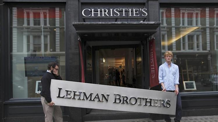 Christie's employees pose for a photograph with a Lehman Brothers sign at Christie's in central London