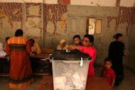 An Egyptian Christian Coptic woman casts her vote at a polling station in the Cairo Coptic Shubra neighborhood. Egyptians voted on Saturday in a run-off presidential election pitting an Islamist against Hosni Mubarak's last premier as the military rulers entered a showdown with the Islamists by disbanding parliament