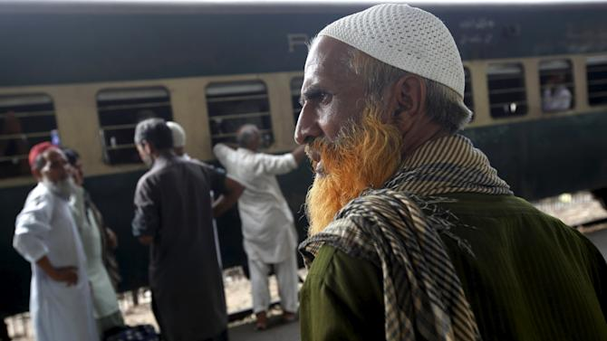 A man with a henna-dyed beard stands with others while waiting for a train to leave at  Cantonment Railways Station in Karachi