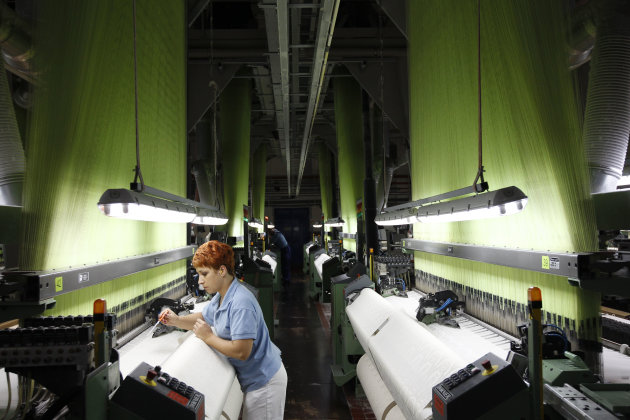 A worker adjusts brocade in a loom at the Veba textile factory in Broumov, Czech Republic, Tuesday, Sept. 25, 2012. When the managers of a textile factory in northern Czech Republic declared they would focus sales on Africa, their bankers, insurers and suppliers shook their heads in disbelief. A decade later, the decision is paying off. While the textile industry in Europe is under pressure from low-cost competition in Asia, the Czech company Veba is working around the clock to meet demand for the high-quality brocade it ships to Muslims and elites in western Africa. The textiles are of a better quality than those shipped in from China and have become a favorite among Africa's Mecca-bound pilgrims. (AP Photo/Petr David Josek)