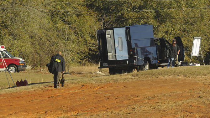Police and emergency personnel remain on site at the property of Jimmy Lee Sykes, a suspect accused of holding a 5-year-old boy hostage in an underground bunker on Saturday Feb.  2, 2013 in Midland City, Ala. Negotiators were still trying to persuade Jimmy Lee Dykes to surrender. Police have said they believe the Lee Dykes, a Vietnam-era veteran,  fatally shot a school bus driver Tuesday, and then abducted the boy from the bus and disappeared into the home-made bunker.  (AP Photo/al.com, Joe Songer)