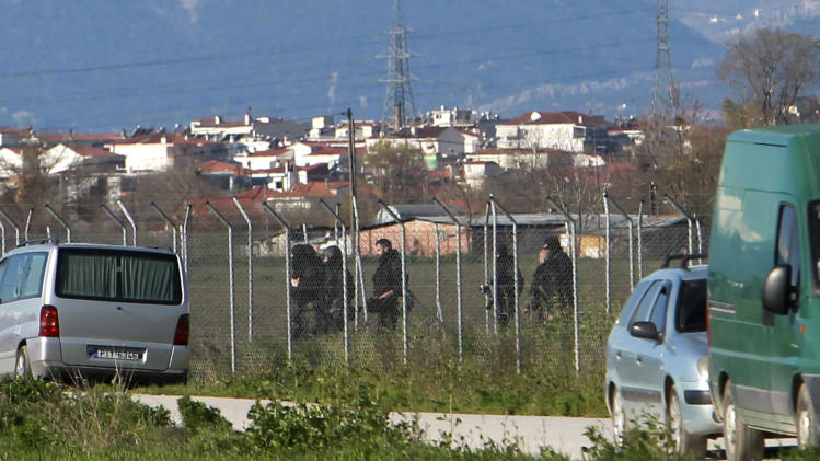 Police officers  patrol  in front of a prison  near the city of Trikala, central Greece, on Saturday, March 23, 2013. At least 11 inmates escaped from a Greek prison after gunmen brazenly attacked the site with grenades and automatic weapons, kicking off a nightlong standoff between police and prisoners. Two guards were injured, one of them seriously. The attack was the latest dramatic incident at Greek prisons, which are suffering from serious overcrowding and staff shortages as the country struggles through financial crisis and a recession that started in late 2008.(AP Photo/Nikolas Giakoumidis)