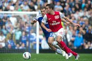 Arsenal's Robin van Persie, challenges for the ball with Chelsea's Branislav Ivanovic during their English Premier League soccer match at the Stamford Bridge ground in London, Saturday, Oct. 29, 2011. (AP Photo/Bogdan Maran)