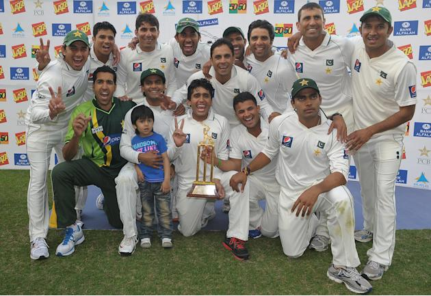 Pakistan's cricketers pose for photographers after  their victory in the third and final Test match between Pakistan and England at the Dubai International Cricket Stadium at Dubai Sports City on