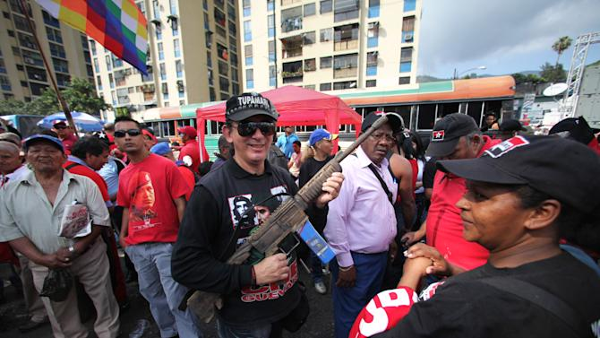 A supporter of Venezuela's President Hugo Chavez holds a fake wooden rifle at an event commemorating the 1958 fall of the country's dictatorship in Caracas, Venezuela, Wednesday, Jan. 23, 2013. Chavez's supporters marched through Caracas in separate groups and gathered in the working-class neighborhood of 23 de Enero, which was built by Gen. Marcos Perez Jimenez, Venezuela's last dictator, and later named for the Jan. 23 date of his downfall. (AP Photo/Fernando Llano)