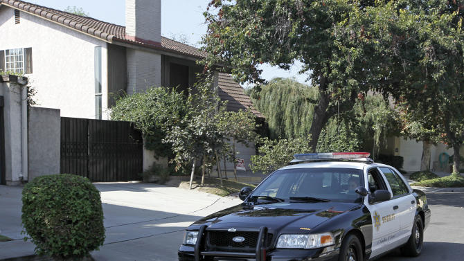 """A Los Angeles County Serriff's deputy in a patrol car passes the home of Nakoula Basseley Nakoula, the man who made the film """"Innocence of Muslims"""" that has sparked violent protests, on a street in Cerritos, Calif., Tuesday, Sept. 25, 2012. The filmmaker has received death threats and was forced into hiding, putting his house up for sale, after the 14-minute movie trailer rose to prominence. (AP Photo/Reed Saxon)"""