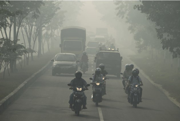 Motorists travel through haze in Pekanbaru, Indonesia's Riau province