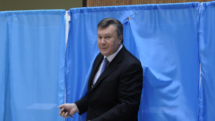 Ukrainian President Viktor Yanukovich leaves a booth for voting at a polling station during parliamentary elections in Kiev, Ukraine, Sunday, Oct. 28, 2012. (AP Photo/Sergei Chuzavkov)